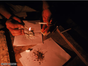 An addict prepares cocaine paste to smoke.
