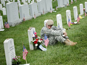 A soldier sits at a grave in Arlington National Cemetery on Memorial Day