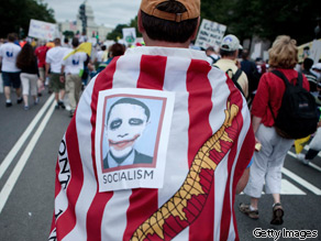 A protester wears an American Revolution-era flag and an Obama picture during the Tea Party Express rally on September 12, 2009 in Washington, DC.
