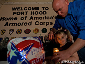 Army Spc. Ryan Hill and daughter, Emma, 3, light a candle Saturday near the main gate of Fort Hood in Texas.