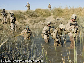 U.S. Marines are pictured wading through a canal in Afghanistan's Helmand Province.