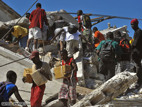 Looters search under the rubble in Port-au-Prince