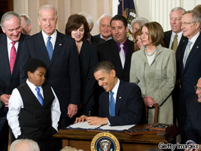 Pres. Obama, surrounded by lawmakers, signs the health care insurance reform legislation in the East Room of the White House on March 23, 2010.