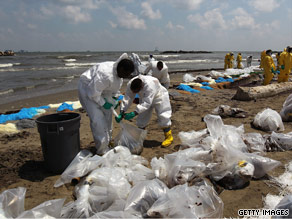 A BP cleanup crew removes oil from a beach Sunday in Port Fuchon, Louisiana.