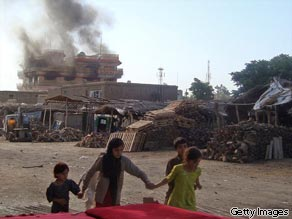 Afghan children walk along a street as smoke rises from a building in Kunduz, Afghanistan on July 2, 2010.