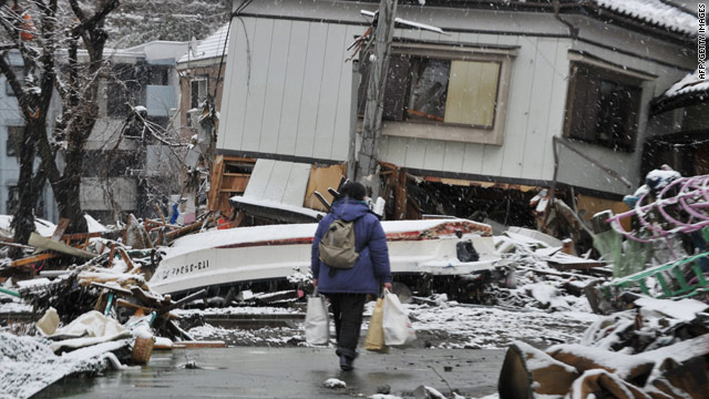 A woman makes her way through earthquake and tsunami rubble Wednesday in Kamaishi, Japan.