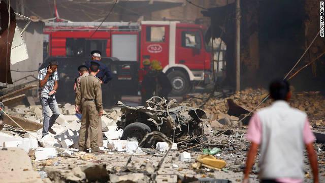 La policía iraquí y bomberos inspeccionan el escenario tras una explosión en la ciudad santuario central iraquí de Karbala.