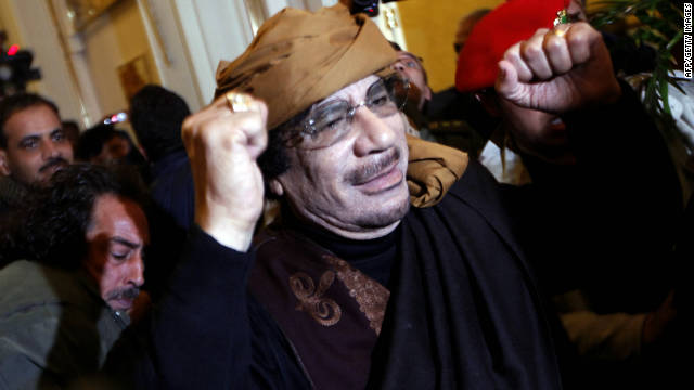 Gadhafi smiles and raises his arms as he enters the Rixos Hotel in Tripoli on March 8, 2011.