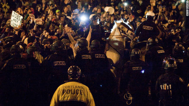 Police attempt to disperse a crowd at Occupy Portland on Sunday.