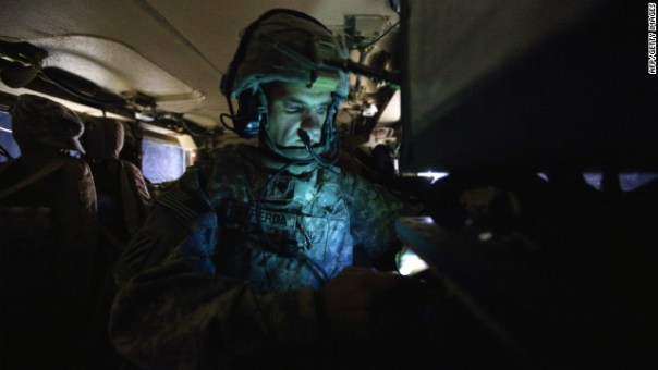 A U.S soldier checks his cell phone while on patrol in Iraq in December. Smartphones are first being deployed to soldiers.