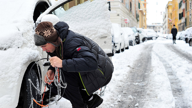 <br/>A man puts snowchains on his car on Saturday, February 4, in Rome. Heavy snowfalls in Rome caused the Italian capital to grind to a halt.