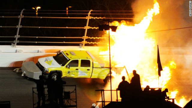 Workers try to extinguish a fire from a jet dryer after it was hit by Juan Pablo Montoya during the Daytona 500.