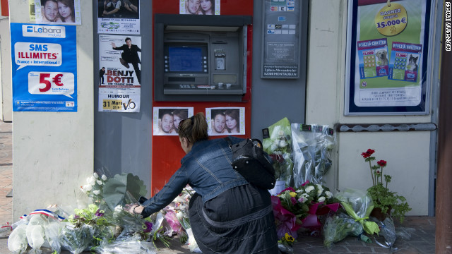 A woman places a bouquet of flowers on March 17, at the site where two French soldiers were killed on March 15, in the French city of Montauban. Prosecutors in Paris have opened an investigation into all three shootings under anti-terrorism powers.