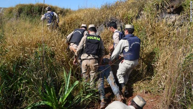 La policía el viernes arrastrar el cuerpo de uno de los campesinos muertos a tiros en el desalojo de ocupantes ilegales en Curuguaty.