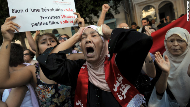 Tunisian women protest Tuesday, October 2, in front of a courthouse in Tunis where a young woman faces charges of indecency by two police officers accused of raping her.