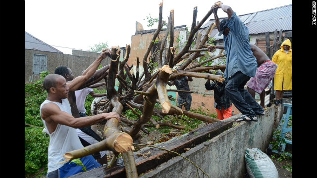 Men deal with downed tree branches after heavy rains caused by Hurricane Sandy in Kingston, Jamaica, on Wednesday, October 24.