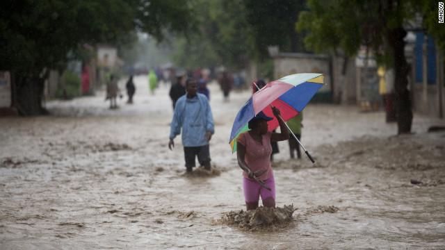 People walk on a flooded street after Hurricane Sandy hit Port Au Prince, Haiti, on Thursday.