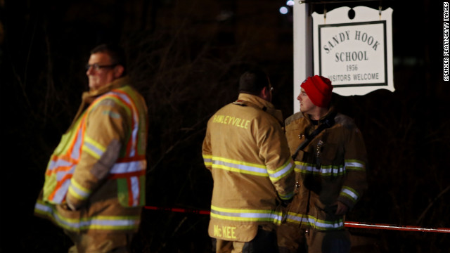 Emergency workers stand in front of the Sandy Hook Elementary School on Friday, December 14 in Newtown, Connecticut. Twenty-seven people are dead, including 20 children, after a deadly shooting rampage.