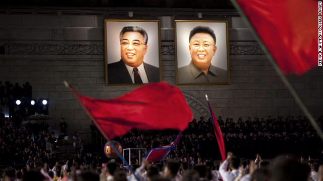 North Koreans wave flags in front of portraits of Kim Il Sung, left, and his son Kim Jong Il during celebrations to mark the 100th birth anniversary of Kim Il Sung in Pyongyang on April 16, 2012.