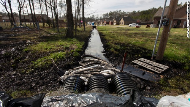 Spilled crude oil is seen in a drainage ditch near evacuated homes in Mayflower, Arkansas, on Sunday, March 31. An Exxon Mobil pipeline carrying Canadian crude oil ruptured on March 29 causing the evacuation of about two dozen homes. Mayflower residents have filed a class-action lawsuit against the company.
