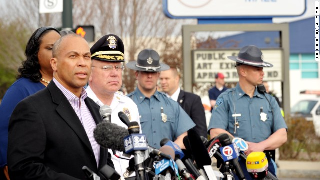 Massachusetts Gov. Deval Patrick, left, speaks to the media at a shopping mall on the perimeter of a locked-down area during the search on Friday.
