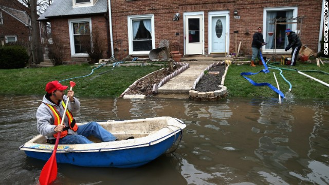 Octavio Castillo paddles down a flooded street on Friday, April 19, in Des Plaines, Illinois, a suburb of Chicago.