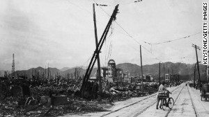 A man wheels his bicycle thorough Hiroshima in August 1945, days after the city was leveled by an atomic bomb blast.