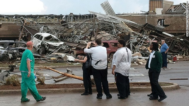 Onlookers stop to view a portion of the destruction delivered by a large EF4 tornado in Moore, near Oklahoma City on Monday, May 20. At least 51 people are confirmed dead in the storm that touched down near Newcastle, Oklahoma, at 2:56 pm CDT carrying winds up to 200 mph.
