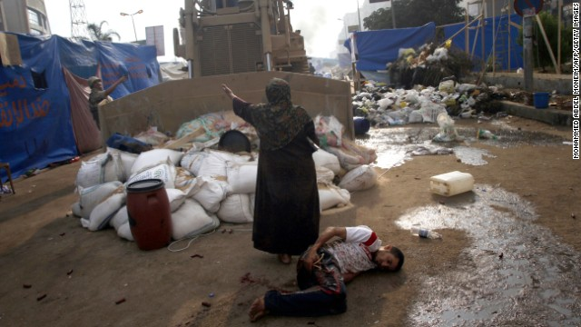 A woman tries to stop a military bulldozer from hurting a wounded youth during clashes on August 14 in eastern Cairo.