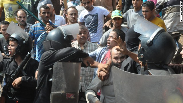 Egyptians security forces escort a supporter of the Muslim Brotherhood out of the Al-Fateh mosque and through an angry crowd in Ramses Square on August 17.