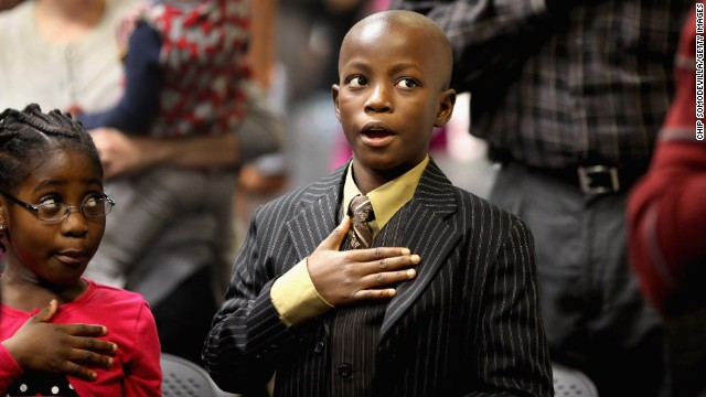 Born in Liberia, Cynthia Newton, left, and her brother, James, say the Pledge of Allegiance during their 2011 citizenship ceremony.
