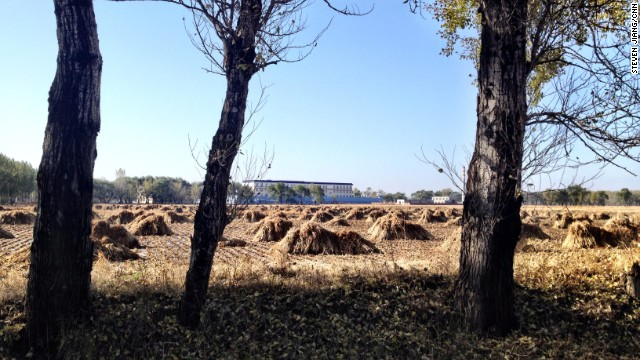 The male inmates' quarters at the Masanjia labor camp stand behind fields covered in haystacks.