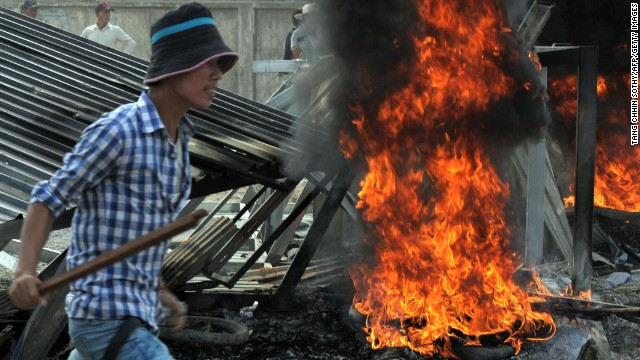 A man armed with a wooden stick rallies during a protest in front of a garment factory in Phnom Penh on January 3.