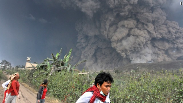 Villagers and a journalist flee as Mount Sinabung erupts Saturday in Indonesia.