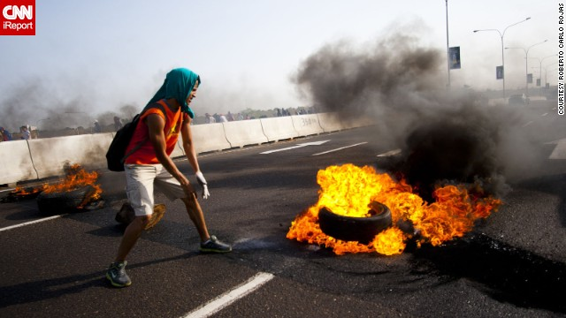 The images of the Venezuela protests spreading online have been a mix of truths and half-truths, with some actually showing other world events. In this verified image, a student in Maracaibo <a href='http://ireport.cnn.com/docs/DOC-1086131'>lights a tire on fire</a> on February 15. Note: The images in this gallery may be disturbing to some.