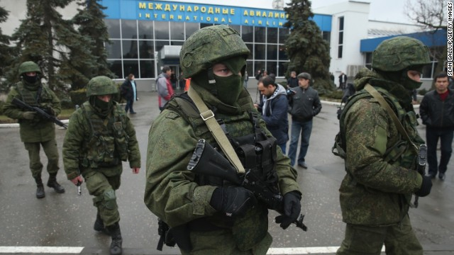 """Armed men patrol outside the Simferopol International Airport in Ukraine's Crimea region on Friday, February 28. The gunmen, whom Ukrainian Interior Minister Arsen Avakov called part of an """"armed invasion"""" by Russian forces, appeared around the airport without identifying themselves. Crimea is an autonomous republic of Ukraine with an ethnic Russian majority. It's the last large bastion of opposition to Ukraine's new political leadership after President Viktor Yanukovych's ouster."""