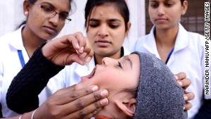 A child receives a polio vaccine from a medical volunteer in Amritsar, India.