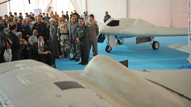 Iranian Supreme Leader Ayatollah Ali Khamenei, seated left, listens to an official during his visit to an aerospace exhibition in Tehran, Iran, on Sunday, May 11. The exhibition revealed an advanced CIA spy drone, at front, captured in 2011 by Iran, and its Iranian-made copy, at back.