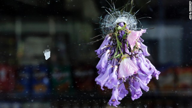 Flowers are placed in a bullet hole in the window of a delicatessen in Isla Vista, California.