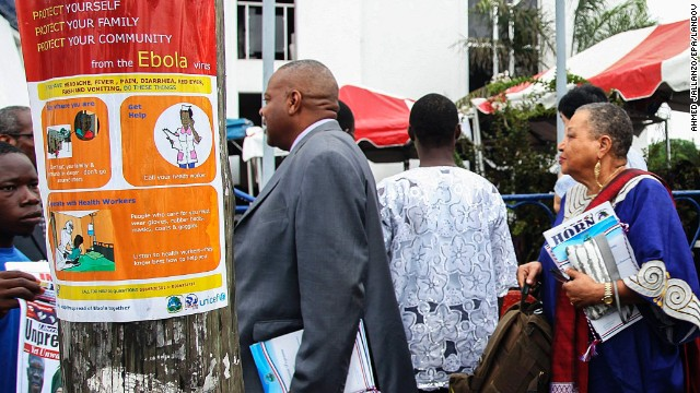 Liberian President Ellen Johnson Sirleaf, right, walks past an Ebola awareness poster in downtown Monrovia as Liberia marked the 167th anniversary of its independence Saturday, July 26. The Liberian government dedicated the anniversary to fighting the deadly disease.