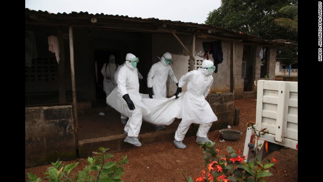 Nurses carry the body of an Ebola victim from a house outside Monrovia on Wednesday, August 6.