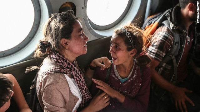 Aziza Hamid, a 15-year-old Iraqi girl, cries for her father while she and some other Yazidi people are flown to safety Monday, August 11, after a dramatic rescue operation at Iraq's Mount Sinjar. A CNN crew was on the flight, which took diapers, milk, water and food to the site where as many as 70,000 people were trapped by ISIS. But only a few of them were able to fly back on the helicopter with the Iraqi Air Force and Kurdish Peshmerga fighters.
