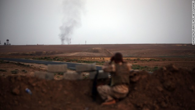 A fighter with Kurdish Peshmerga forces battles ISIS militants near Mosul on Monday, August 18.