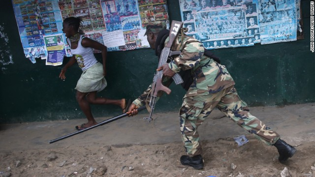 An Ebola Task Force soldier beats a local resident while enforcing a quarantine on the West Point slum on August 20.