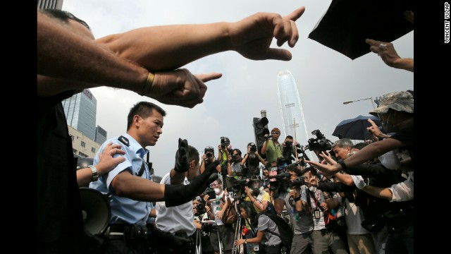 Police raise hands against protesters as an ambulance tries to leave the compound of the chief executive office in Hong Kong on Friday, October 3.