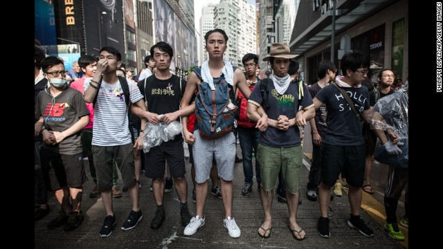 """Pro-democracy demonstrators protect a barricade from """"anti-Occupy"""" crowds in Hong Kong on October 3."""