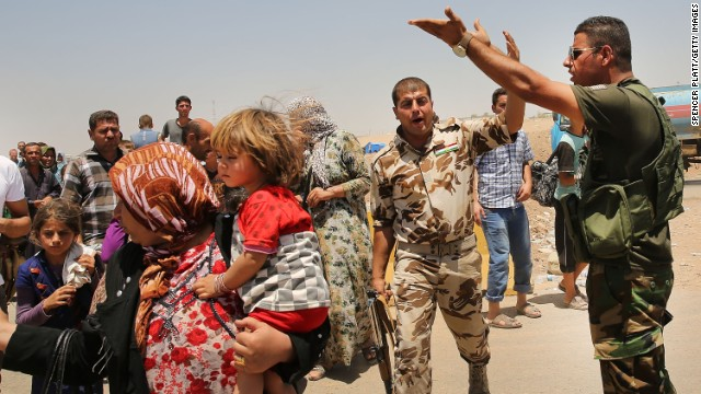 Iraqis who fled fighting in the cities of Mosul and Tal Afar try to enter a temporary displacement camp in Khazair on Wednesday, July 2.