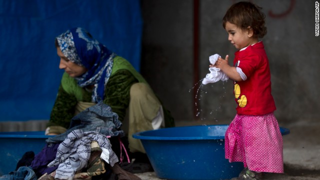 A Kurdish child from the Kobani, Syria, area holds laundry at a refugee camp in Suruc, Turkey, on Monday, November 17. Tens of thousands of people have fled Kobani, known in Arabic as Ayn al-Arab, to escape ISIS.