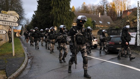 French police special forces walk down a street in Corcy, France, on January 8.