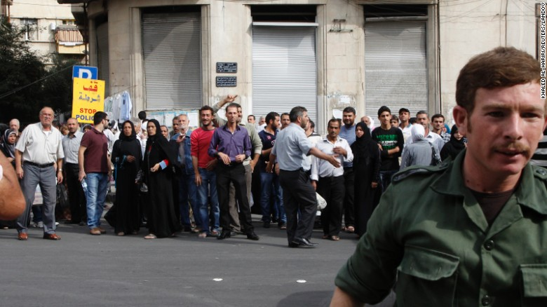 Relatives of Syrian detainees who were arrested for participating in anti-government protests wait in front of a police building in Damascus on October 24, 2012. The Syrian government said it released 290 prisoners.
